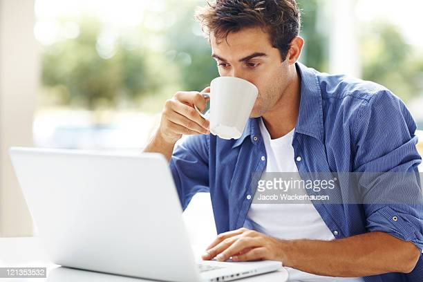 Young man drinking coffee while using at laptop