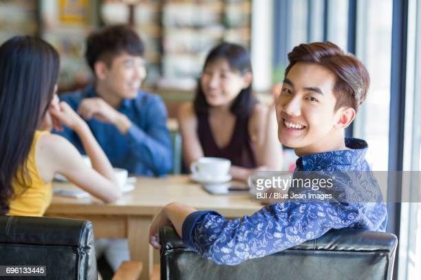Young man drinking coffee with friends in cafe