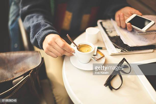 Young man drinking espresso and texting in a cafe