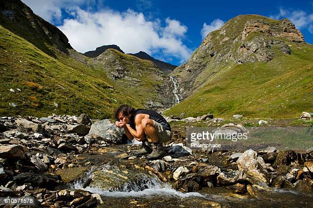 young man drinking freshwater from natural spring in dolomite mountains