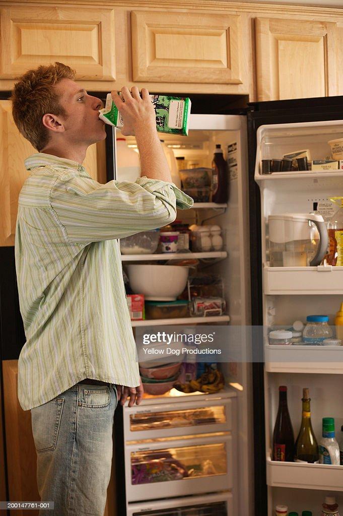 Young man drinking from milk carton, near open refridgerator