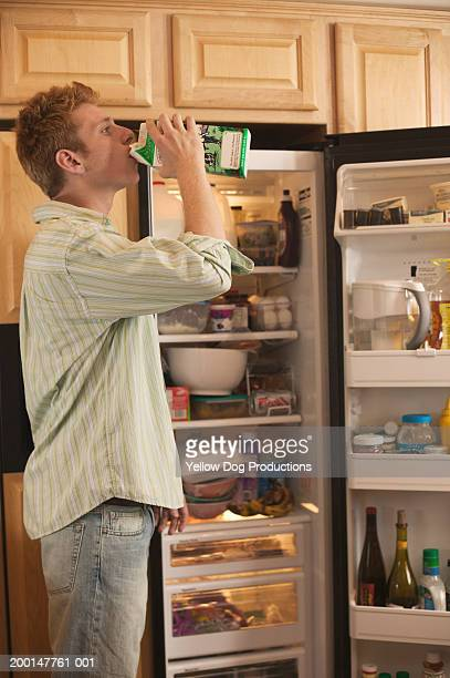 Young man drinking from milk carton, near open refridgerator