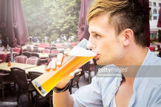 Young man drinking tall glass of beer
