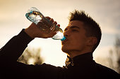 The young man sportsperson is drinking water from bottle outdoors.