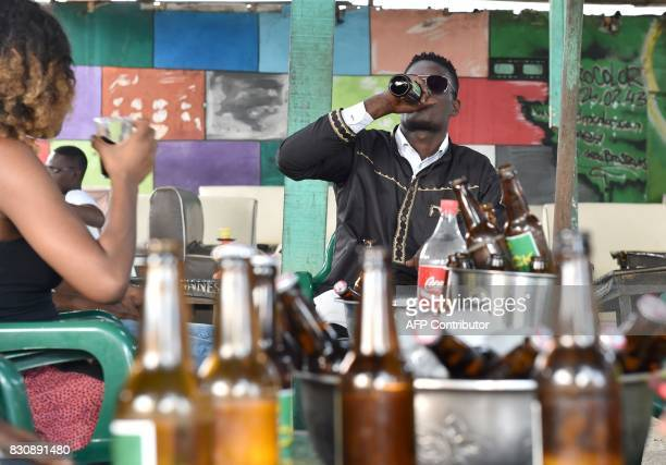 A young man drinks from a beer bottle at a bar in Abidjan on July 13 2017 On posters and huge billboards around the country rival ads by two...