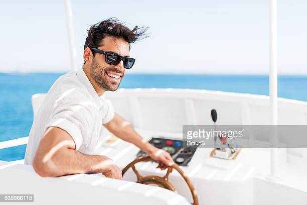 Young man driving a boat.