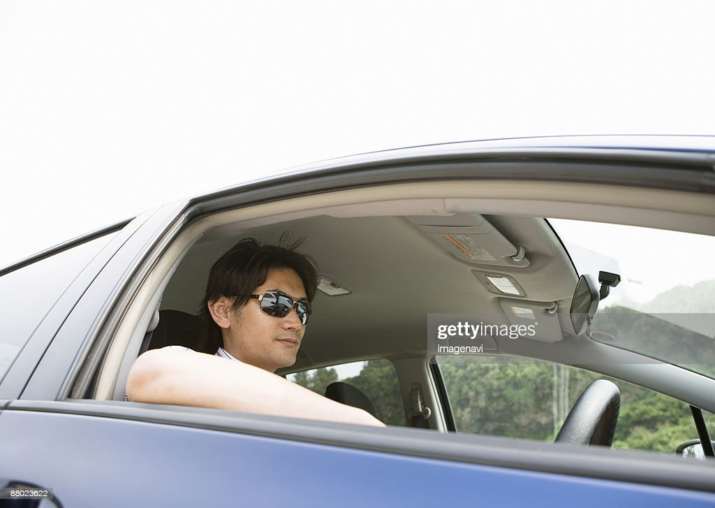 A young man driving a car