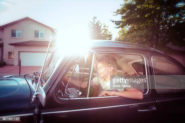 A young man driving along a suburban street