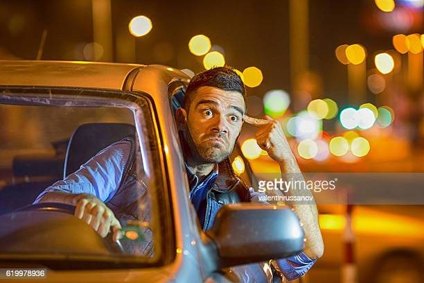 Young man driving car at night angry to traffic