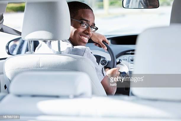 Jeune homme au volant d'une voiture