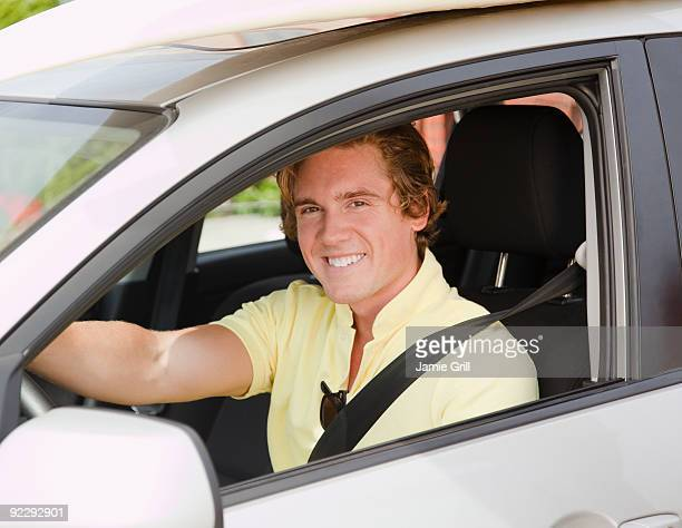 Young man driving car with surfboard on roof