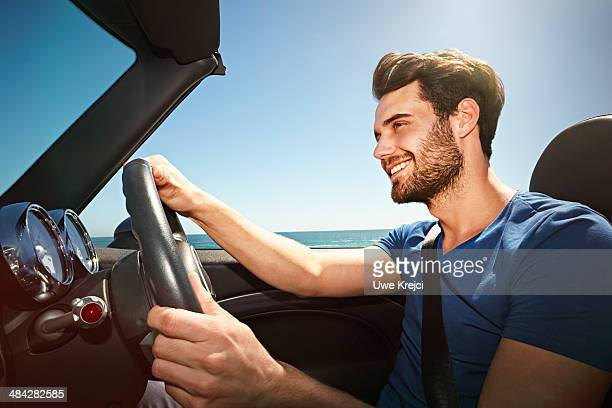 Young man driving convertible by the sea