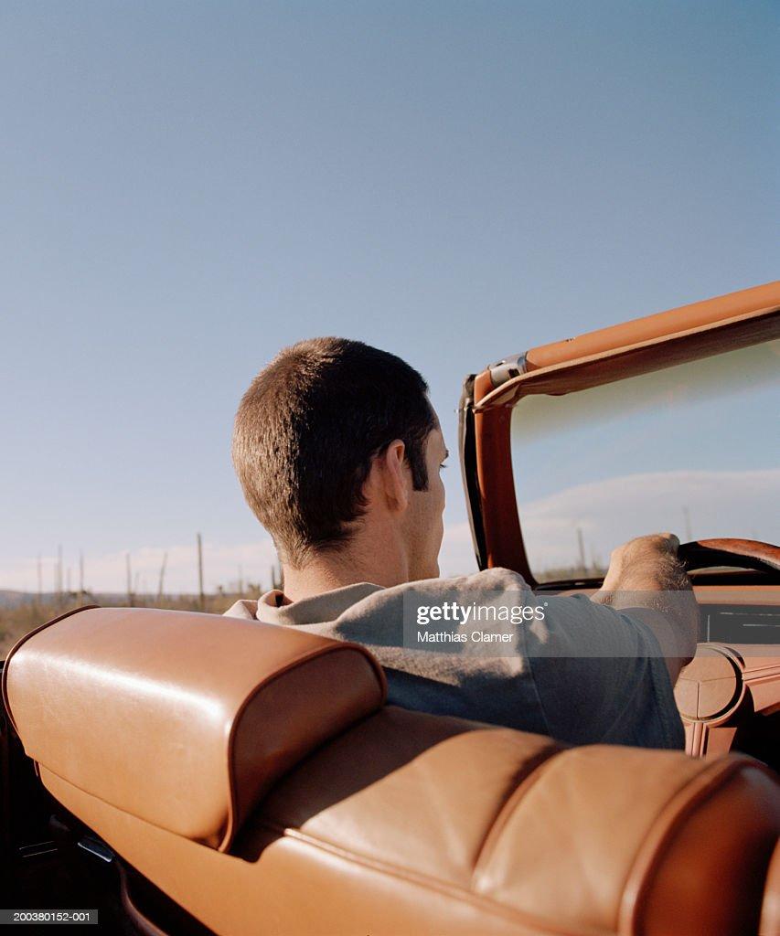 Young man driving convertible, rear view, close-up : Stock Photo