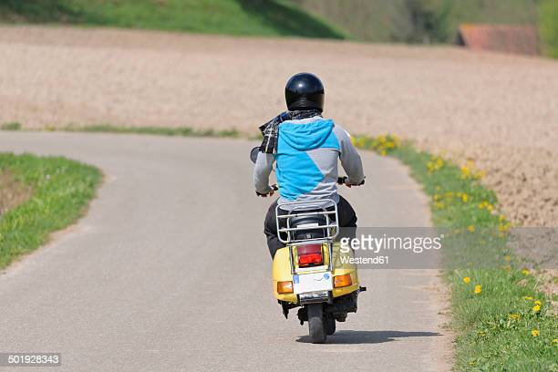 Young man driving with his Vespa on country road