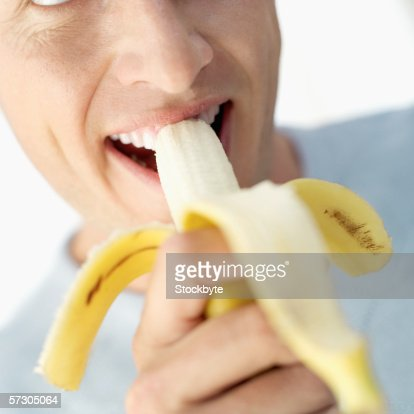Young man eating a banana : Stock Photo
