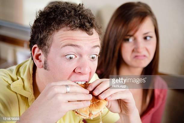 Jeune homme manger un Cheeseburger