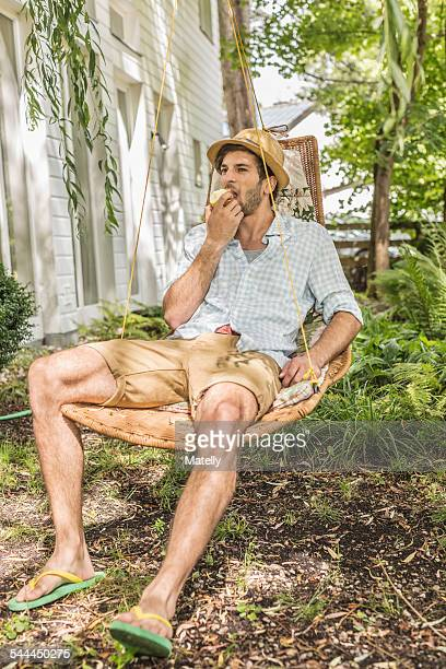 Young man eating apple sitting on hammock in garden