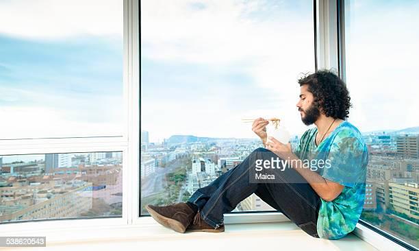 Jeune homme manger des nouilles asiatiques