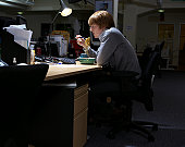Young man eating at desk in dark office, with lamp, side view