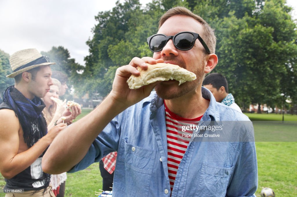 Young man eating at hot dog in the park : Stock Photo