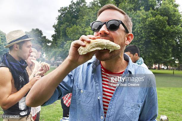 Young man eating at hot dog in the park