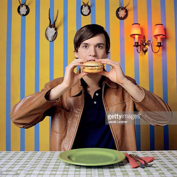 Young man eating burger, portrait