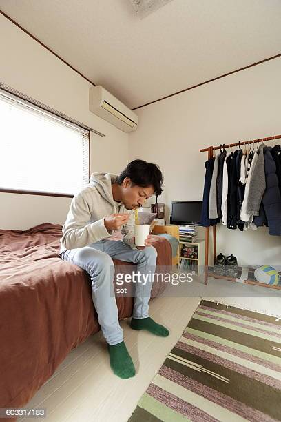 Young man eating cup noodles sitting in bed