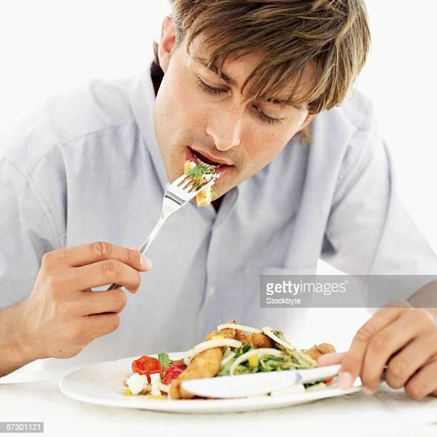 Young man eating fried fish and salad with a fork