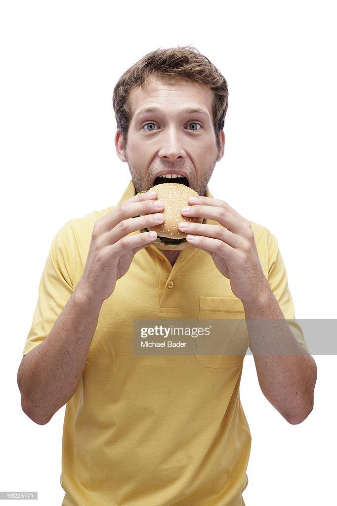 Young man eating hamburger, portrait, close-up