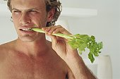 Young man eating lettuce