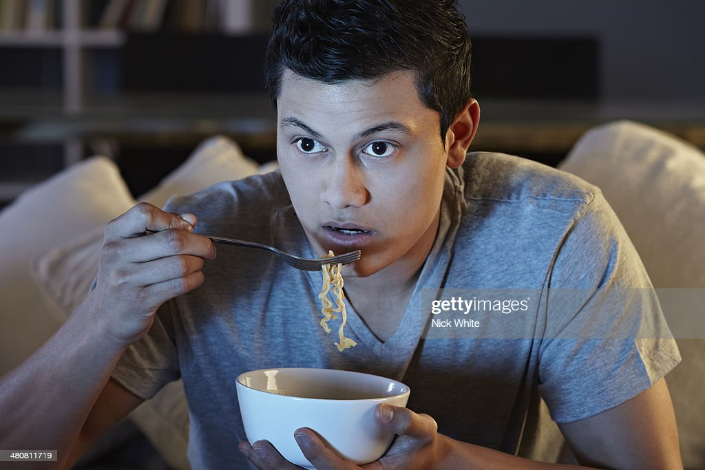 Young man eating noodles and watching tv