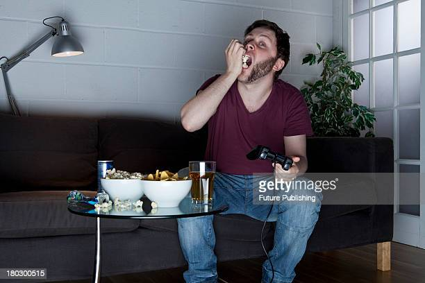 A young man eating popcorn while playing Sony PlayStation 2 video games on a sofa taken on July 9 2013