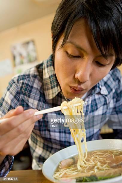 Young man eating ramen noodles