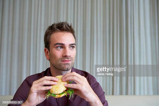 Young man eating sandwich in restaurant, close-up