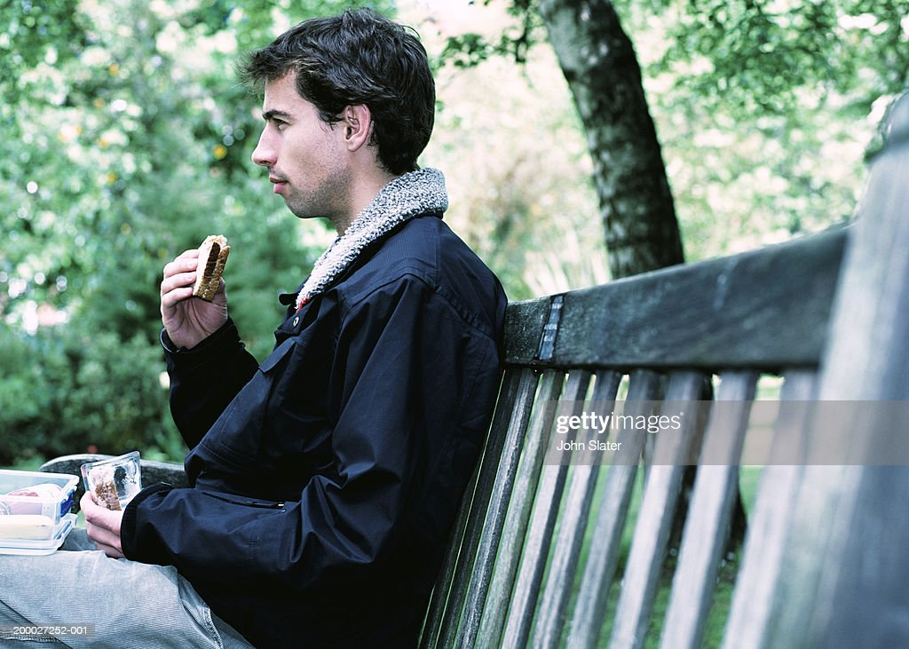 Young man eating sandwich on park bench, profile : Stock Photo