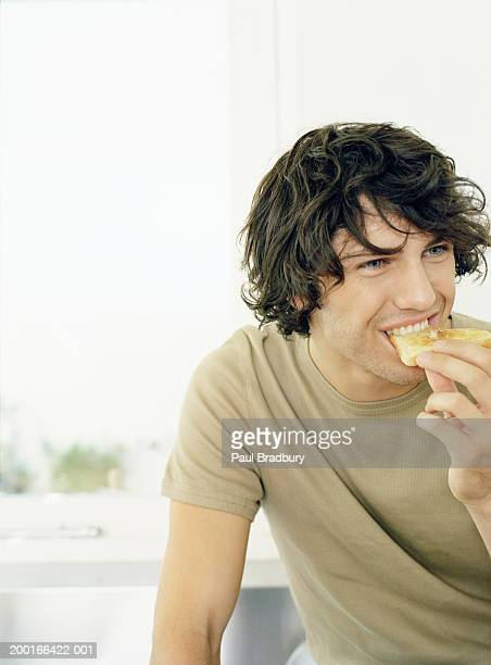 Young man eating toast
