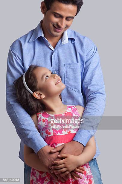 Young man embracing daughter from behind against gray background