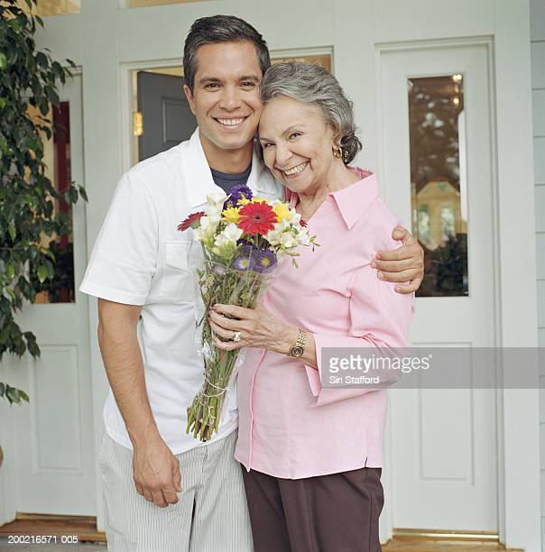 Young man embracing grandmother in front of house