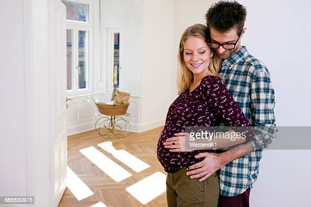 Young man embracing pregnant woman in new home with pram in background
