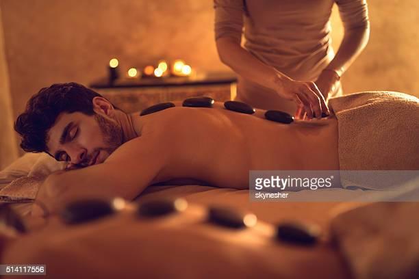 Junger Mann, genießen, während die heiß stone-Therapie im Spa.