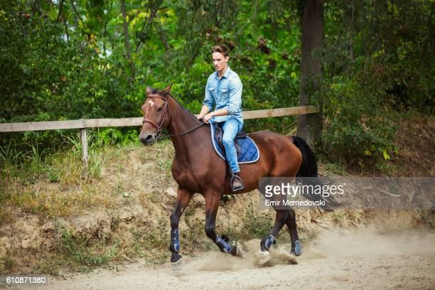 Young man enjoying horseback riding in nature.