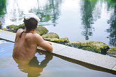 Side view of young man with white towel on his head is enjoying hot sulfur water in outdoor onsen ( hot spring) near Niseko on Hokkaido. In background are trees and grey sky of cloudy and rainy weathe