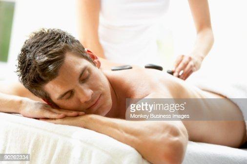Young Man Enjoying Hot Stone Treatment : Stock-Foto