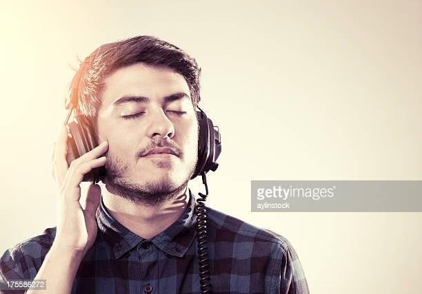 Young man enjoying music with eyes closed
