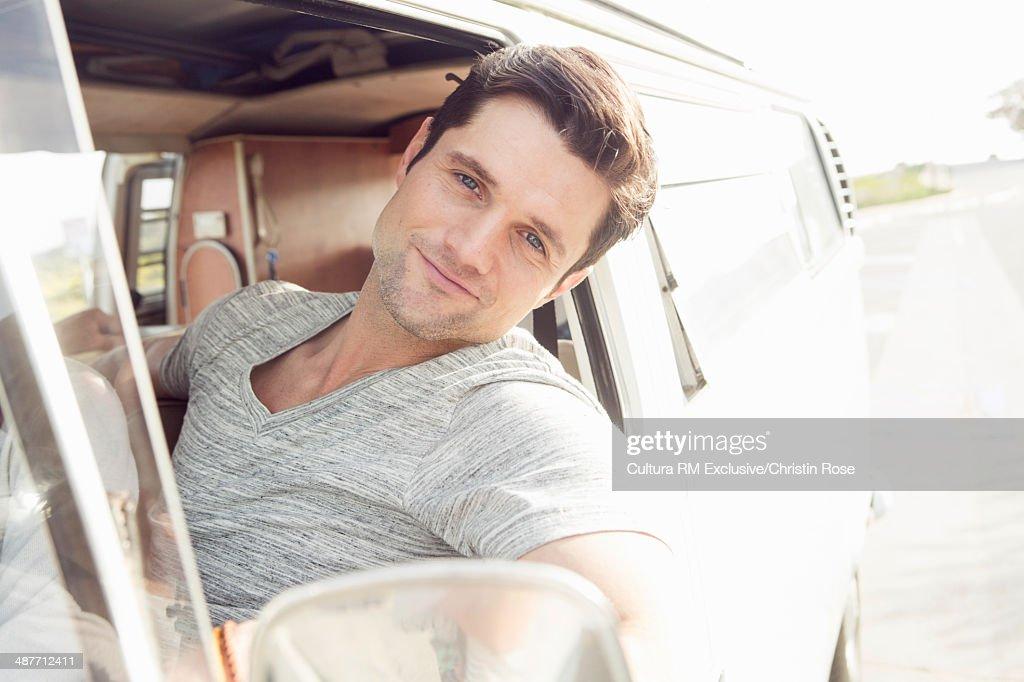 Young man enjoying road trip in a camper van : Stock Photo