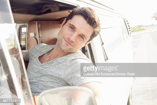 Young man enjoying road trip in a camper van : Stock Photo