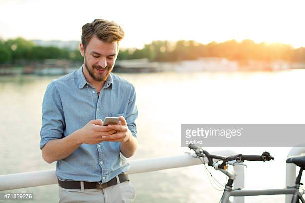 Young man enjoying sunset by the river.