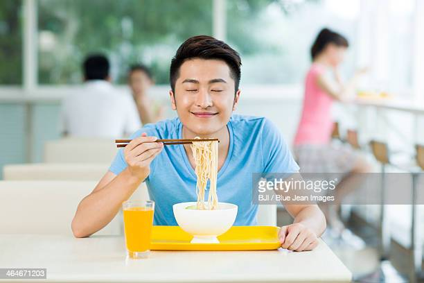 Young man enjoying the smell of noodles