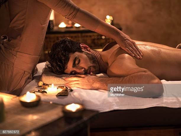 Young man enjoying with eyes closed during back massage.