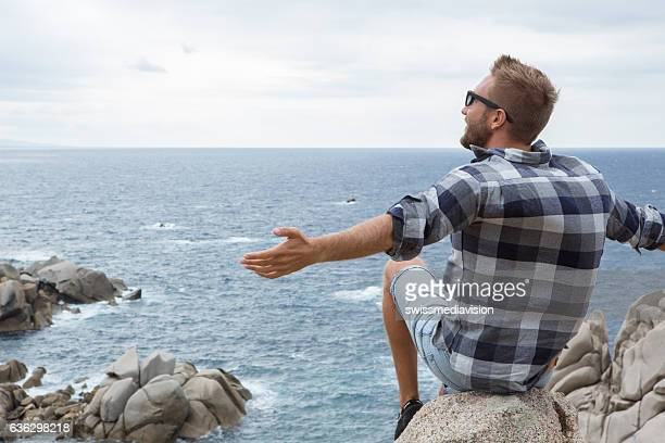 Young man enjoys freshness of the sea